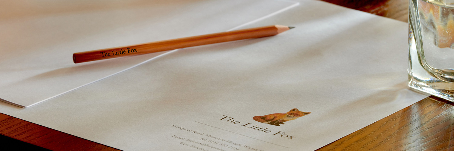 A close up of a Little Fox event venue table, with a business place setting including placemat and pencil.