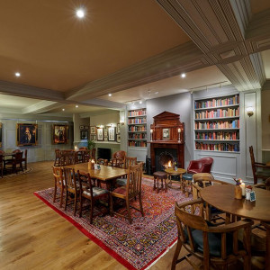 The tables, rug, bookcase and open fire of the bar area
