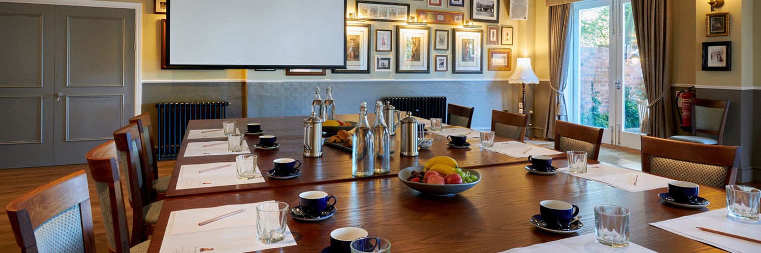 Board room table with business place settings including coffee, water, fruit and pastries with projector screen in the background.