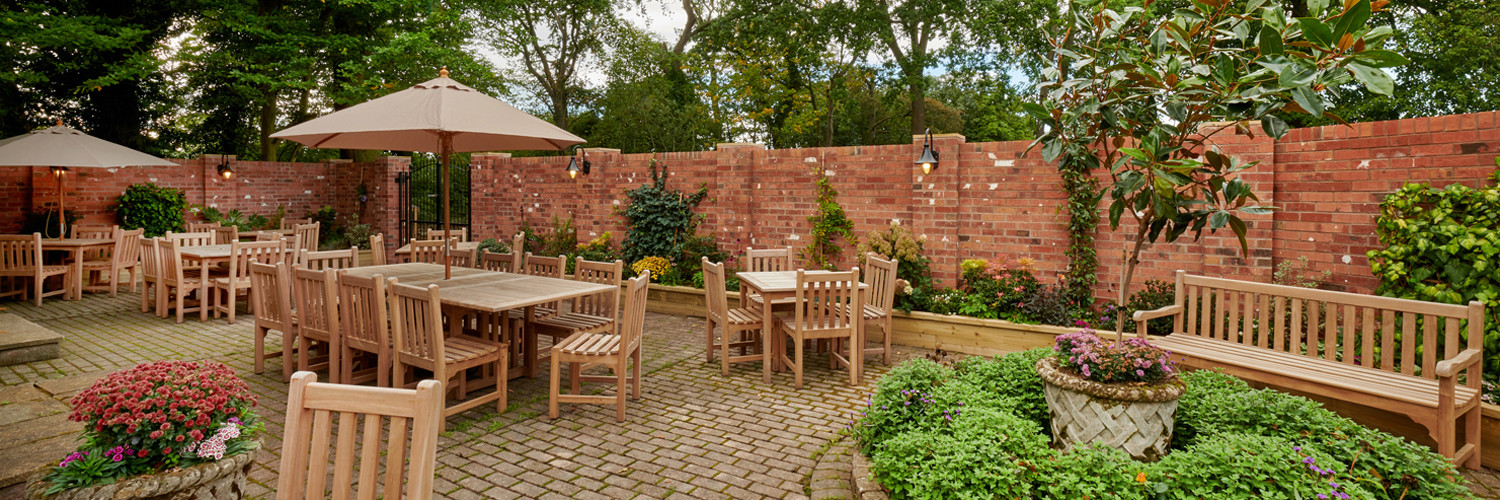 Walled, private, terrace area with a border of shurbs and outside furniture