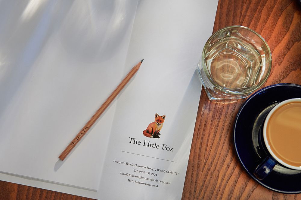 Close up photo of a meeting table with a water glass, coffee cup and note pad and pencil with the Little Fox logo