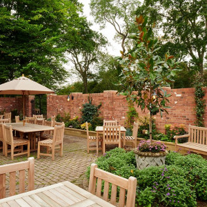 The large private outside terrace with wooden tables and chairs, a border of shrubs and mature trees in the background