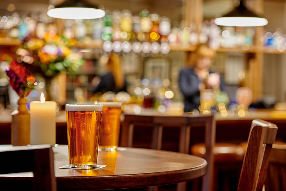 Two pints of lager on a bar table with lady pulling a pint from a well stocked bar in the background