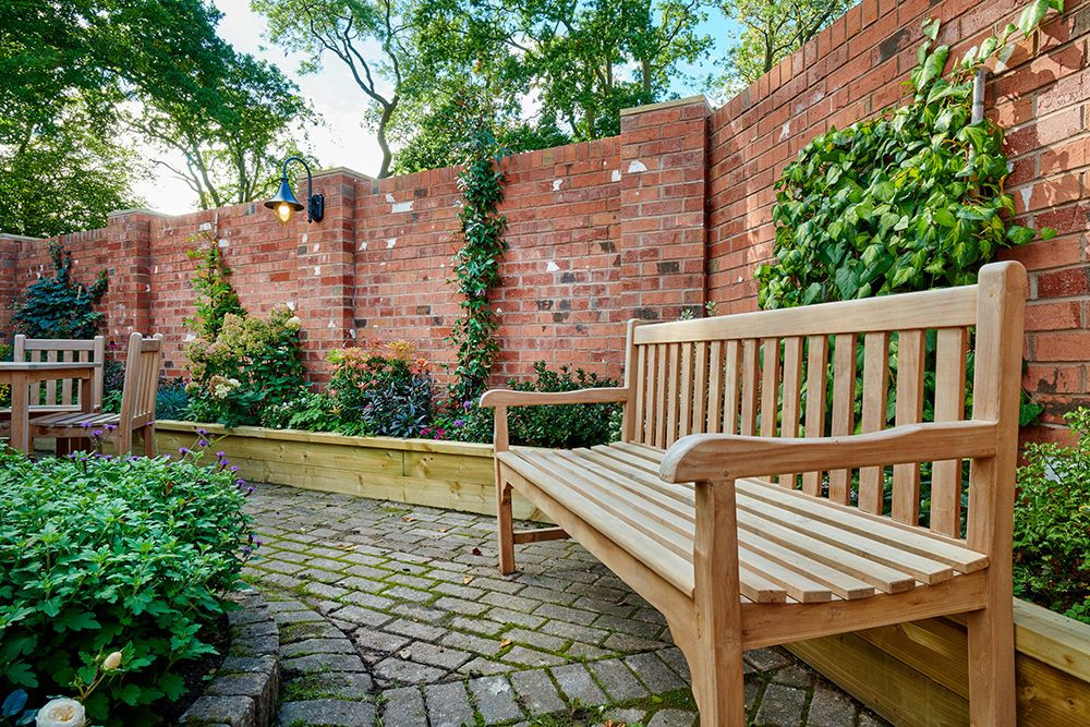 Wooden bench with red brick wall, ivy and other mature shrubs in an attractive border