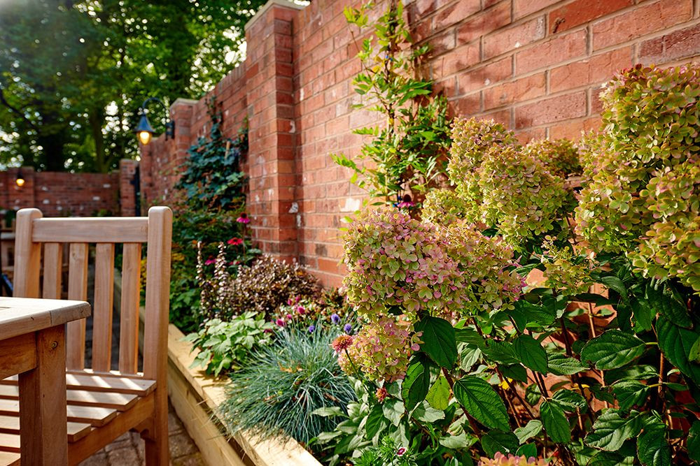 Outside terrace with wooden tables and a planted border with a wall