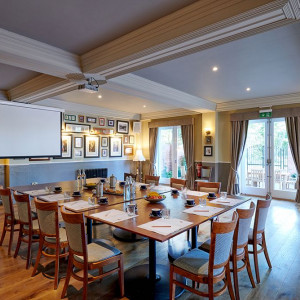 A spacious meeting room with tables in a boardroom layout and projector from the ceiling