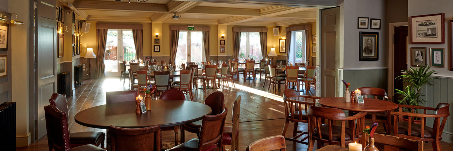 The view from the bar with the internal doors open to the larger function room. Tables and chairs in both rooms with large windows in the background