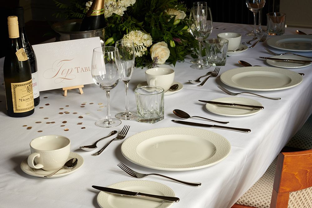 A wedding table laid up ready for service with flowers, confetti and wine glasses