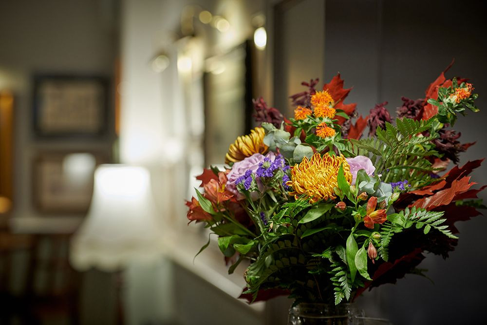 A vase of fresh flowers with a floor standing lamp and picture frames in the background