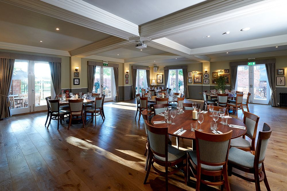 Looking across the dining room showing round tables laid ready for a large dinner party