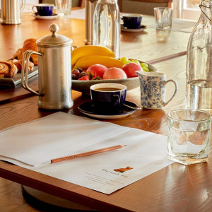 A table set for a business meeting with pastries, fruit and fresh coffee
