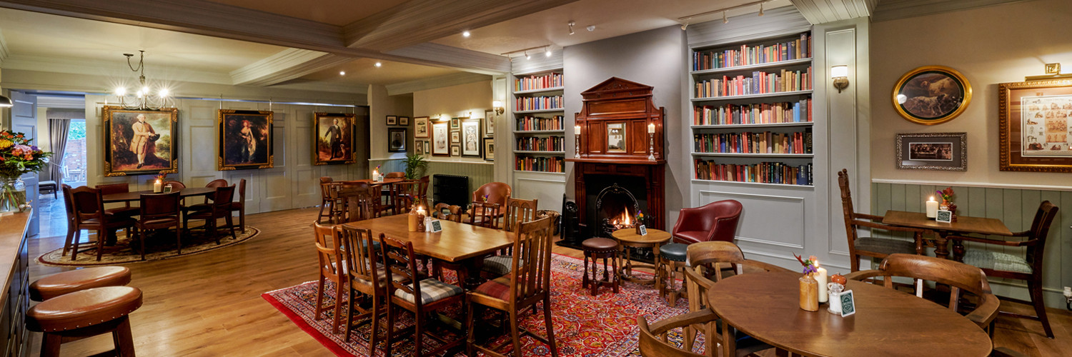 The private pub area with tables, oil paitings, book cases and rugs
