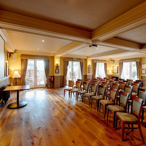 Large event venue with hard wood floor large windows, projector screen and chairs arranged in theatre style