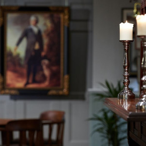 A photo showing room details. A wooden mantlepeice with candles in the foreground and an oil painting hanging in the background